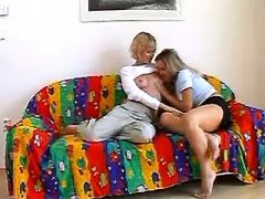 Lesbians caress each other on sofa