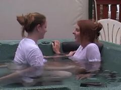 Two beautiful lesbians kiss and caress in pool